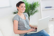 Smiling woman sitting on a couch and using a laptop
