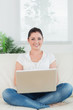 Smiling woman using a laptop and sitting on the couch