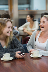 Women sitting at the college coffee shop while laughing