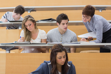 Students sitting at the lecture hall while teacher explaining