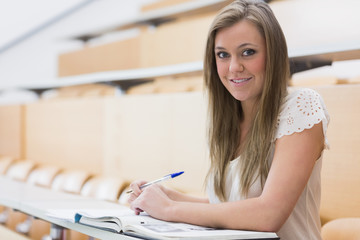 Girl sitting while smiling in the lecture hall