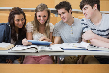 Students sitting looking at tablet pc and smiling