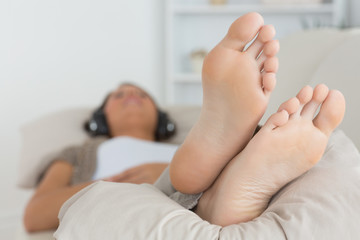 Woman with her feet up listening to music
