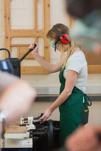 Woman standing at a drilling machine