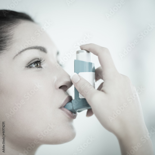 Woman with asthma using the inhaler