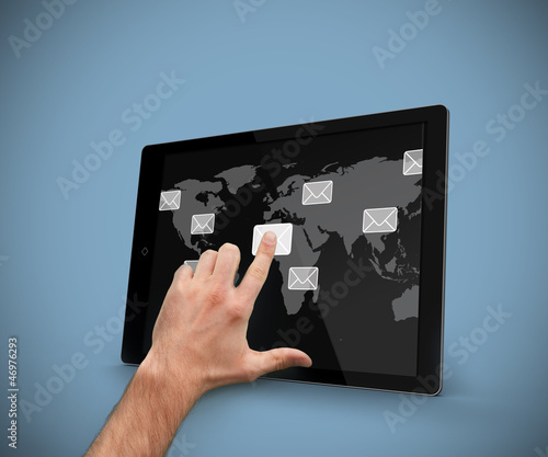Hand pointing at tablet computer with email symbols