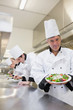Cheerful chef showing his salad with workers in background