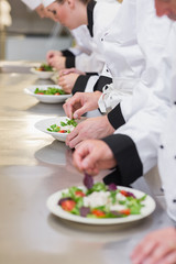 Chef's team garnishing salads