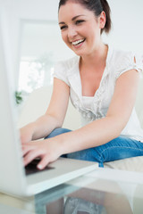 Laughing woman on the couch using a laptop