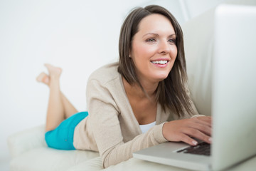 Woman using her laptop and looking happy
