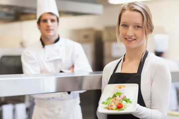 Smiling waitress carrying salmon plate