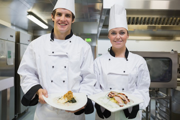 Two smiling Chef's showing plates