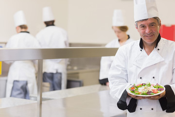 Smiling chef presenting his salad