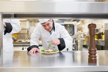 Smiling chef garnishing salad
