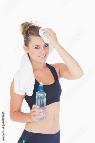 Woman standing while holding a towel to her forehead