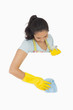 Smiling woman in gloves cleaning white surface