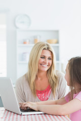Woman and daughter sitting at the kitchen smiling with a laptop