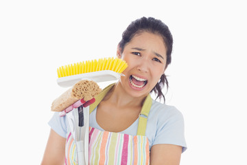 Frightened woman holding mop and a broom