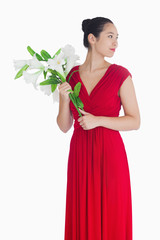 Woman in red dress holding lilies