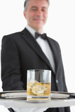Man holding glass of whiskey on tray