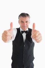 Well-dressed waiter having thumbs up