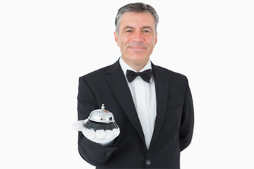 Man in suit holding hotel bell