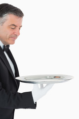Waiter looking and holding a silver tray
