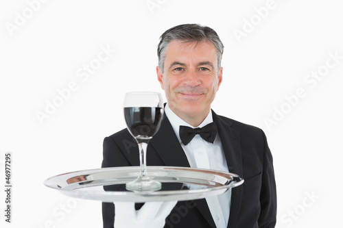 Smiling waiter holding a glass of wine on a silver tray