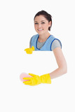 Cheerful maid washing with a sponge