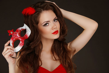 Beautiful Woman with red lips holding Carnival mask in hand.