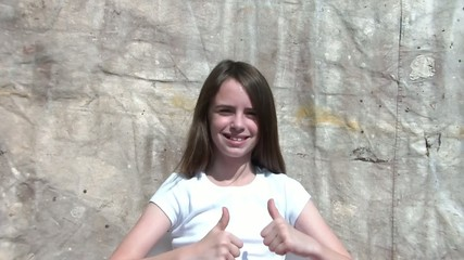 Girl Gives Two Thumbs Up and Smiles