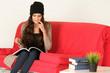 Junge Frau sitzt auf ihrer bequemen Couch