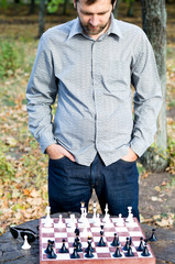 Man standing contemplating a chessboard