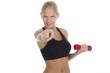 Sportliche Frau mit roter Hantel zeigt auf jemanden