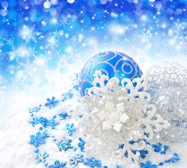 Christmas blue and silver decorations on snow on a festive backg
