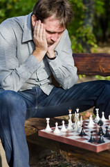 Despairing man looking at a chessboard