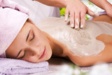 Young woman with slimming body thermal mask on her back. Spa Tre