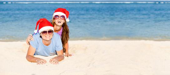 beautiful couple in santa hats on tropical beach.panorama