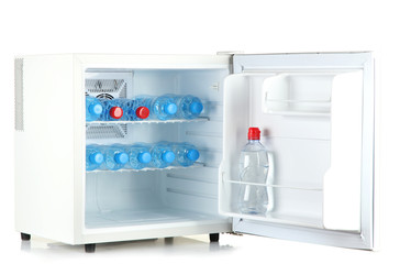 mini fridge full of bottled water isolated on white