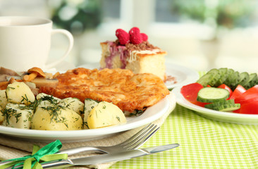 Roast chicken cutlet with boiled potatoes and cucumbers, cup of