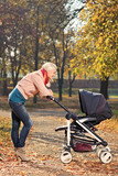 A young mother looking at her baby in a stroller