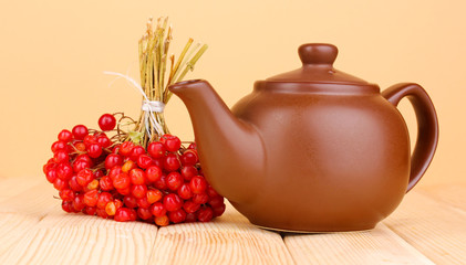 tea with red viburnum on table on beige background