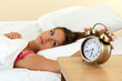 young beautiful woman in bed and alarm clock