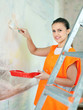 Female house painter paints wall