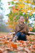 Happy woman throws autumn leaves