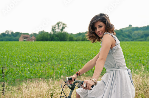 Beautiful young woman portrait with bike in a country road.