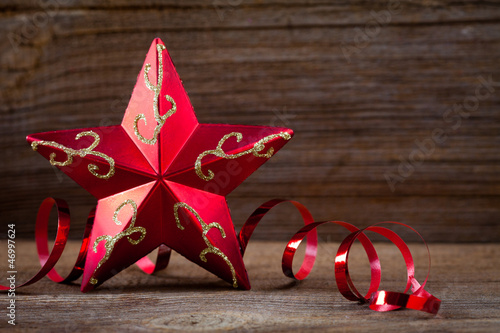 red star , gifts and ribbons on weathered wooden board