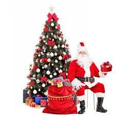 Santa Claus with a gift sitting next to a bag, christmas tree in