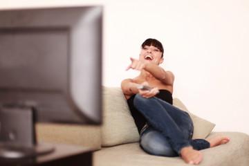 Hübsche frau lacht über das Fernsehprogramm
