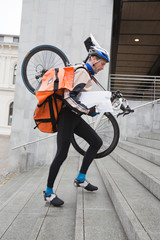 Courier Delivery Man With Bicycle And Backpack Walking Up Stairs